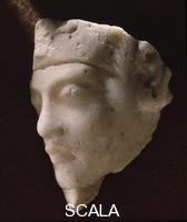******** Limestone fragment with face with corkscrew-curl wig in Amarna style.