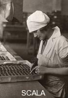 ******** A woman uses a piping bag to decorate chocolates, Rowntree factory, York, Yorkshire, 1932.