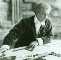 ******** Frank Lloyd Wright, in corduroy suit, seated at drafting table, 1924.