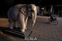 ******** An elephant statue adorns the well kept square near a temple. Southeast Asia.