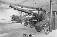 ******** LCC-LFB fire station appliance room with engines. A typical London Fire Brigade appliance room at the turn of the twentieth century. From left to right are the horse drawn steamer, the horse drawn escape cart and a manual hose cart. Also shown are the hor